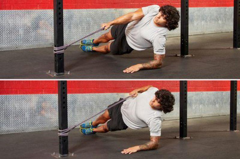 Nghiêng mình sang 1 bên sao cho thân mình vuông góc với sàn khi tập Plank nghiêng giữ dây co giãn